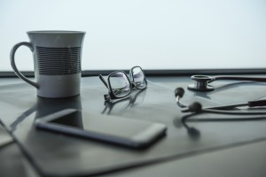 The doctor's desk with the mug, smarthphone, stethoscope and eyeglasses.